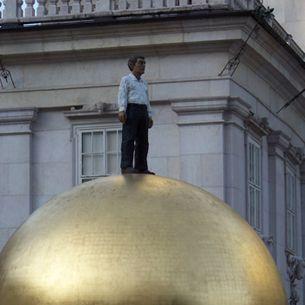 Mensch auf goldener Kugel